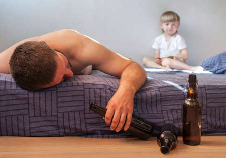 A drunk man in the morning lies on the bed with a bottle of alcohol in his hand. Hangover Syndrome. Alcoholism concept