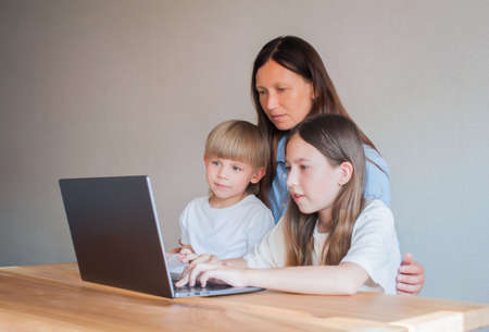 Happy mom with two children are sitting at home at the table with a laptop. Distance learning of children. Mom helps children learn remotely