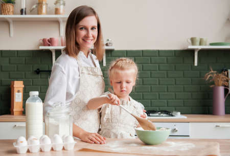 Happy mother and her little daughter kneading dough together at home in the kitchen