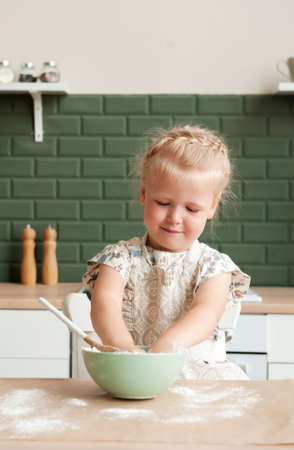 Little happy girl prepares dough in the kitchen. Child pastry chef in the kitchen Stock fotó