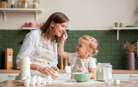 Happy mother and her little daughter knead dough together at home in the kitchen. Little girl helping mom to cook in the kitchen