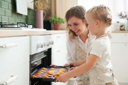A young blonde woman takes out ready-made cookies from the oven in the kitchen at home. Home confectioner. homemade baking