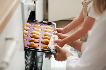 The woman and her little daughter get ready-made cookies from the oven at home. Close-up