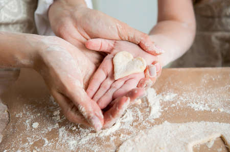 Mom and daughter are holding a heart made of dough. Together they cook cookies in the kitchen. Close-up Stock fotó