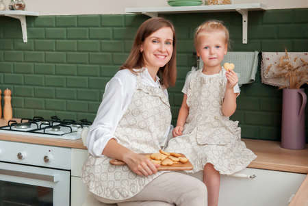 Young happy mom and little daughter eating heart shaped cookies in the kitchen at home