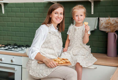 Happy slender young woman in an apron with a mug and cookies is sitting at home in the kitchen. Young hostess in the kitchen. Cooking cookies at home. Pastry chef girl Stock fotó