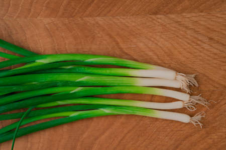 Bouquet of fresh green onions on a wooden board. Healthy vegetarian food. Close-up. View from above
