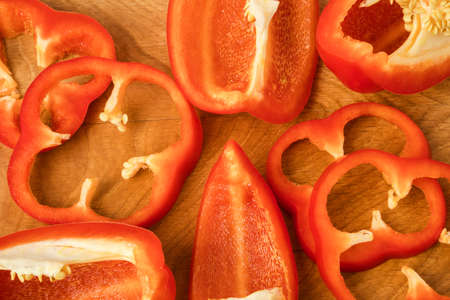 Sliced pieces, parts, lobes of sweet pepper, red, on a wooden board