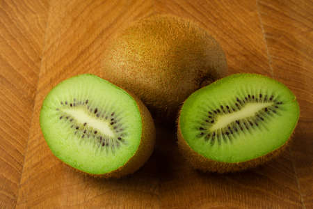 Kiwi one whole and one cut in half lie on a wooden board Reklamní fotografie