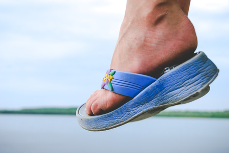flipflops: Child foot wearing flip-flops in air and landscape view