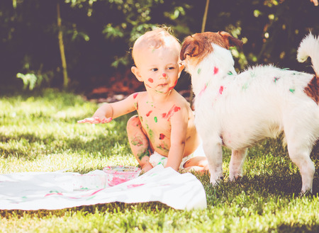1 year old baby painting on his body and on dog