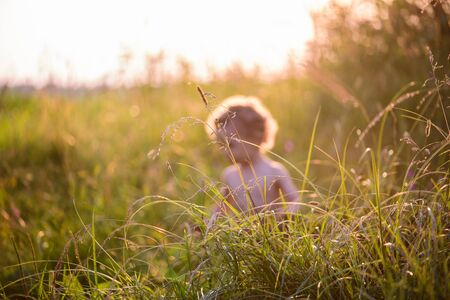 Little angel with aura walking and playing in grass at sunset