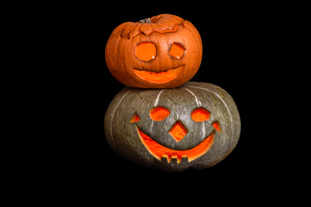 frightful: Two stacked Halloween pumpkins with smiley faces on black background Stock Photo