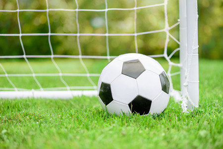Classic football (soccer) ball on green grass ground in front of white goal with net