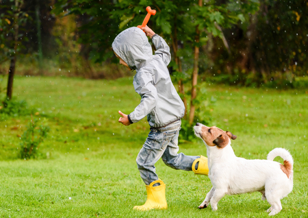 Kid boy wearing waterproof coat playing with a dog