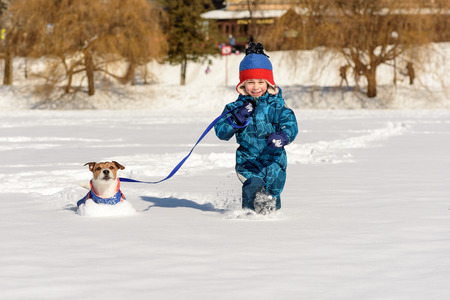 Kid and dog playing on snow