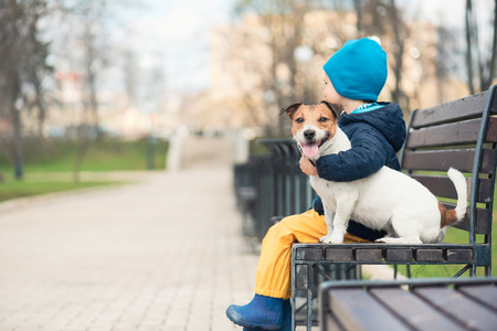 Domestic animal concept with boy hugging his pet dog Banque d'images