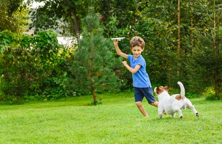 Kid playing with paper airplane and dog outdoors Stok Fotoğraf