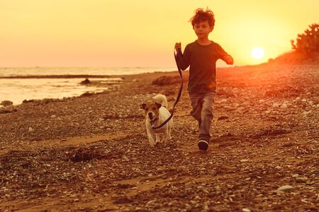 5 years old kid and dog running at autumn beach