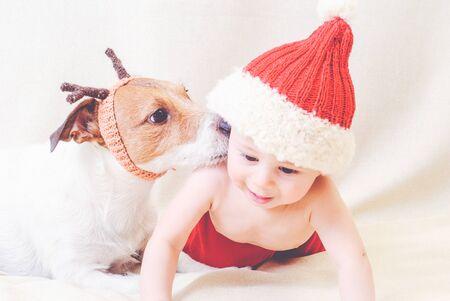 Dog wearing reindeer antlers kissing baby in santa claus costume Foto de archivo - 133450329