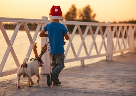 Holidays at beach concept with child and dog wearing Christmas and New Year costumes at seafront
