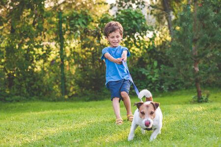 Small boy and dog training to walk on leash without pulling