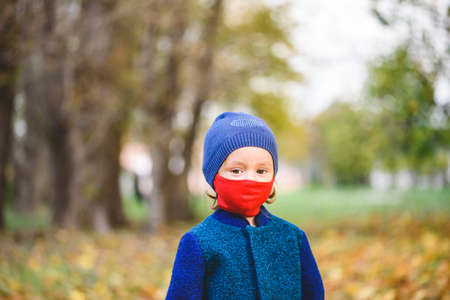 Concept of new normal with little girl in red protective face mask and warm clothes walking in autumn park 免版税图像