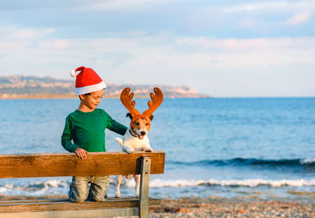 Boy in Santa Claus hat and dog in costume of Rudolph reindeer at winter beach in South Europe Stock Photo