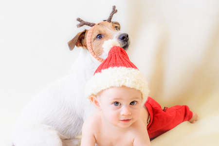 Little funny baby in Santa Claus costume and dog with reindeer antlers enjoying Christmas holiday celebration Stock Photo