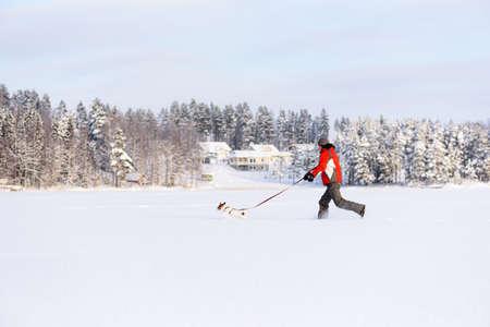 Running man walking dog has fun outdoors on snow on bright winter day