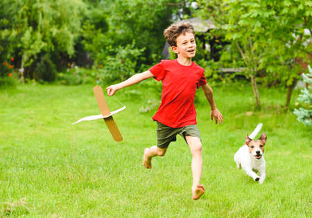 Kid boy playing with DIY cardboard plane dreaming to be pilot
