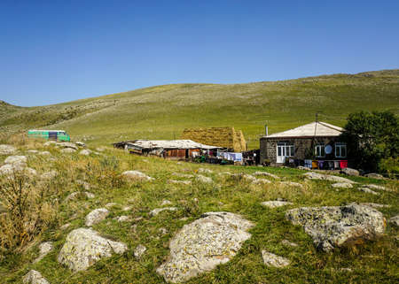 Lake Arpi Village House with Rocks Grass Land in Summer and Blue Sky