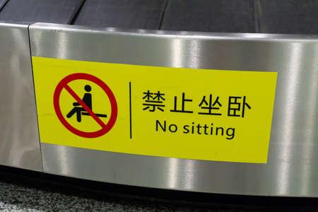 No Sitting Warning Sign at Multi Level Baggage Carousel Luggage Claim Hall
