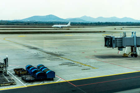 One Airplane Taxiing at Airport Airstrip with View of Apron Drive Airbridge