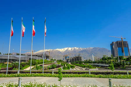 Tehran Ab-o Atash Park with View of Snow Capped Mount Tochal Alborz and Four Iranian Waving Flags