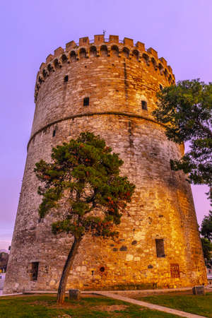 Thessaloniki White Tower Frontal View with Trees and Blue Sky Cloudy Background at Sunset