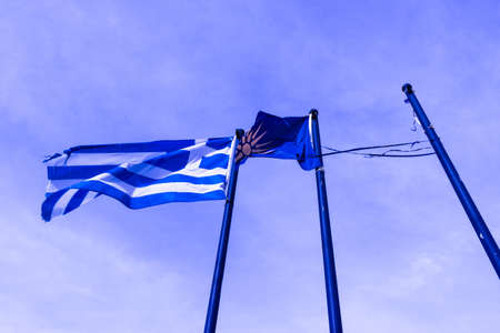 Greek and Blue Colored Macedonian Vergina Sun Flag Waving on Flagpoles Stock Photo