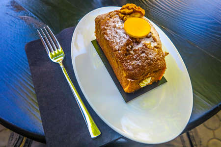 Ukrainian Traditional Carrot Cake with Powder Sugar on a White Oval Plate with a Fork