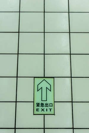 Dark Green Colored Arrow Sign in English and Chinese on the Tiles Floor