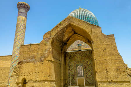 Samarkand Gur-e Amir Complex Mausoleum Ruined Arched Bow Gate with Minaret View 스톡 콘텐츠