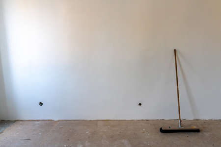 Common Black Colored Horsehair Sweeping Broom Leaning on a White Color Painted Wall in an Apartment with Empty Sockets for Electrical Power