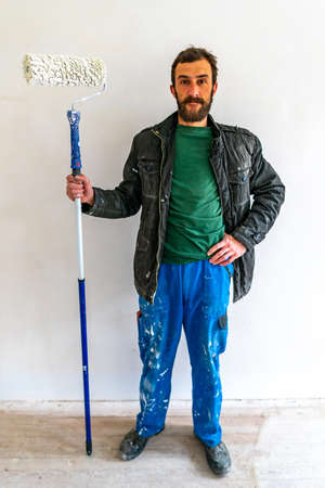 Young Caucasian Brown Haired Man with Beard and Blue Colored Dungarees Working Trousers Standing and Holding his Fabric Paint Stick Roller Extension Pole at White Colored Wall Background