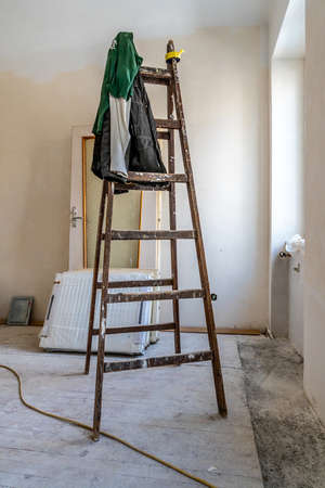Empty Wooden Ladder with Hanging Dirty Green Colored Pullover Clothes in a White Color Painted Wall Apartment Room Under Construction next to the Window Stok Fotoğraf