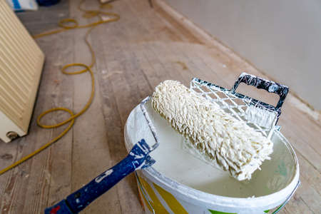 Fabric Mini Roller with Plastic Paint Grid Equipment Standing on a Bucket with White Color Wall Painting Closeup with Yellow Colored Electrical Power Hose at Background Stok Fotoğraf