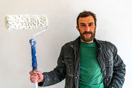 Young Caucasian Brown Haired Man with Beard and Blue Colored Dungarees Working Trousers Standing and Holding his Fabric Paint Stick Roller Extension Pole at White Colored Wall Background Closeup Stok Fotoğraf