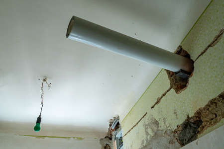 Open Sewage Pipe Under Construction Hanging on White Color Painted Ceiling with Common Old Fashioned Green Colored Light Bulb at Background at an Apartment