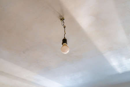 Common Old Fashioned Light Bulb Hanging on White Color Painted Ceiling which is Illuminated by Sun Rays from the Window