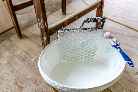Bucket Closeup Filled with White Color Wall Painting a Paint Brush with Plastic Grid Equipment and Wooden Ladder at Background Stok Fotoğraf
