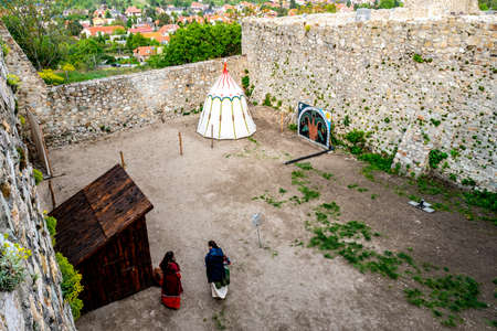 Devin Castle with Two Women dressed in Medieval Clothes and White Colored Middle Ages Shelter at Courtyard with Town Sight at Background