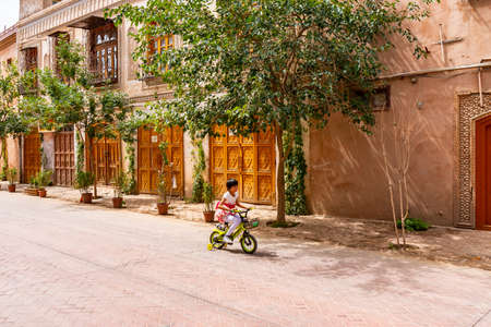 Kashgar Renovated Old City Uyghur Girl is Driving a Bicycle down the Street on a Sunny Blue Sky Day